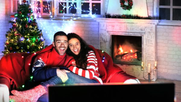 Smiling young couple having fun at home, watching TV together and laughing. Both wears warm clothes and sitting on sofa. On background lights on decorated christmas tree, windows and burning fireplace, steel candlestick on ground. Back of TV set on foreground.